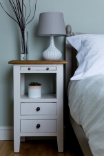 The neat vintage style bedside tables add a rustic charm and feature a pull out shelf to allow an extra surface. The ceramic bedside lamps have been paired with soft linen shades.