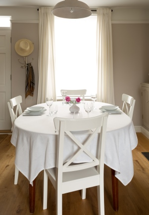 Soft greys and whites create a calm and elegant dining room. New oak flooring was installed and these Ikea chairs give a slightly Scandinavian feel. An antique industrial pendant light creates a contrast with the soft white curtains.