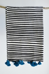 Black and white stripe blanket with blue pom poms, £90.00 from Decorator's Notebook