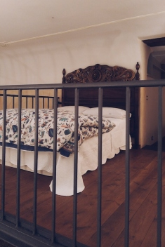 The beautiful bed on the mezzanine. Check out that headboard!